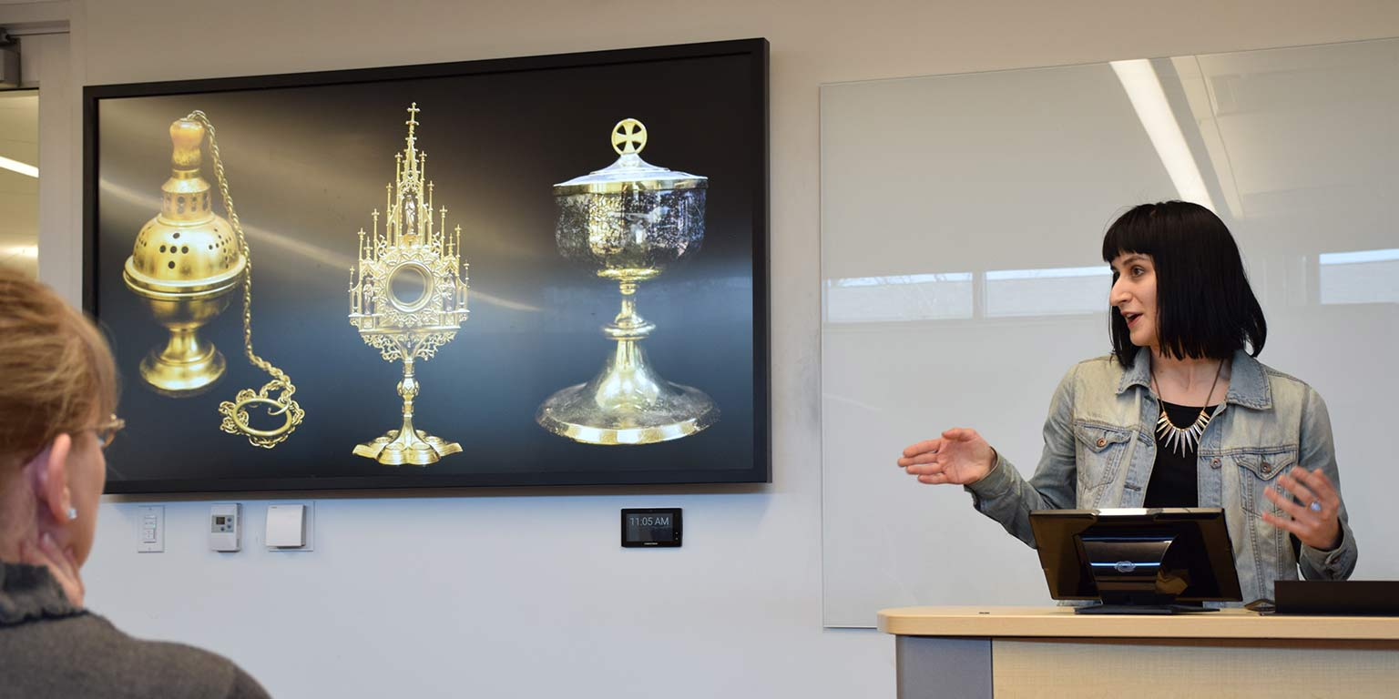 A woman with short black hair stands behind a lectern, gesturing towards a powerpoint slide that shows gold artifacts.