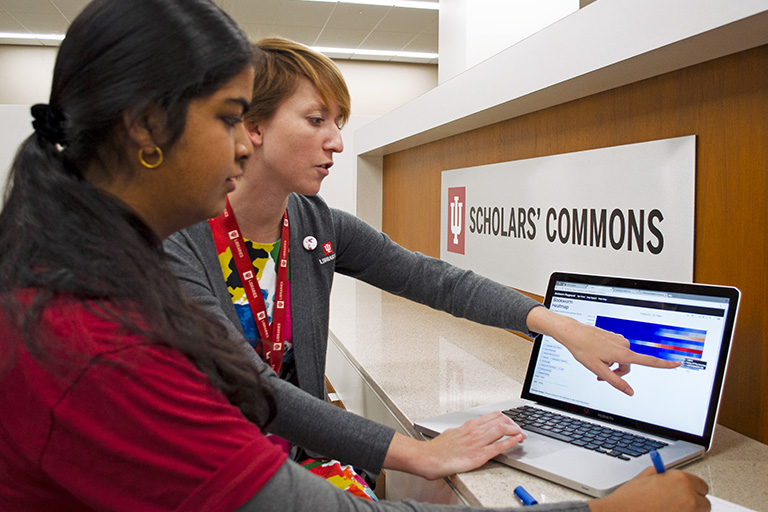 "Two woman standing in front of a ""Scholars Commons"" sign look at a computer; one woman is gesturing toward the screen."