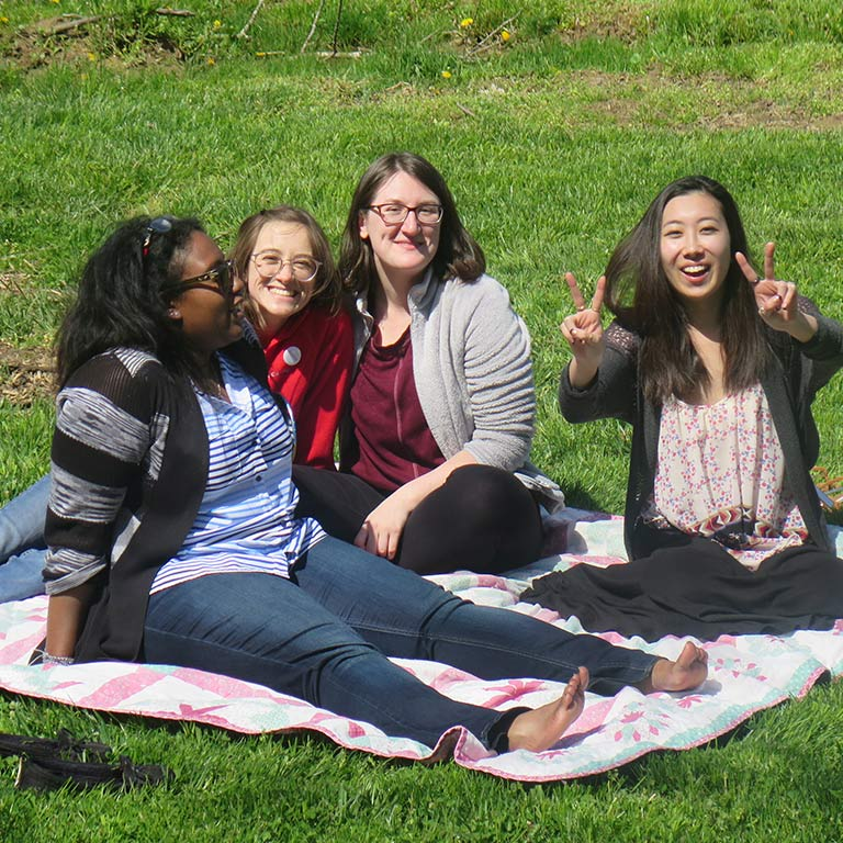 Four female students sit on a green lawn laughing; one is flashing a peace sign with her fingers to the camera.