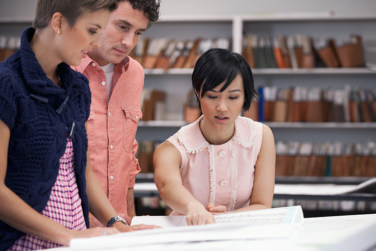 An open map is spread out on a desk; one student points at the map while two others look to see what she's pointing at.