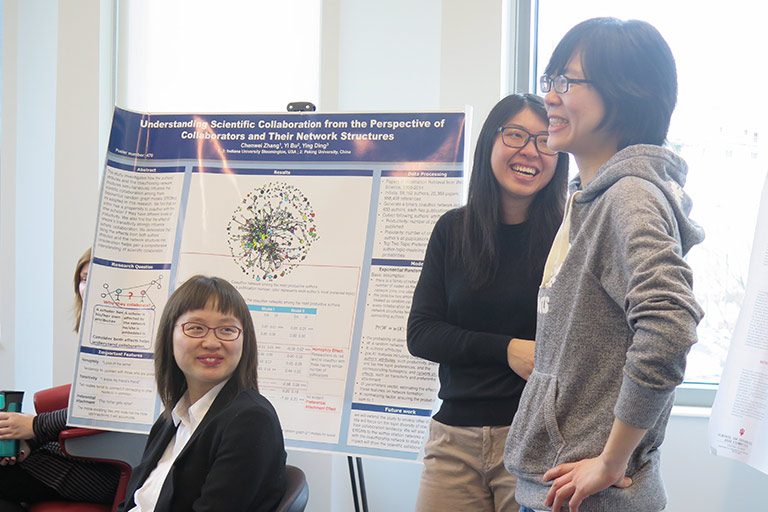 Three students stand in front of an easel showing off their research.